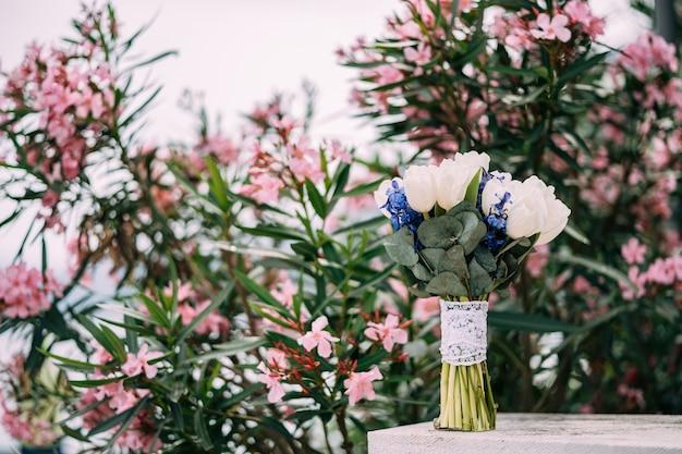 Brautstrauß aus weißen tulpen rittersporn salal limonium und spitzenbändern in der nähe des blühenden rosas