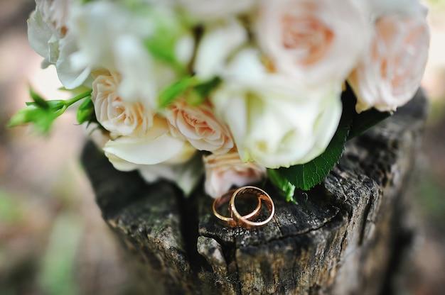Brautstrauß mit eheringen auf dem stumpf