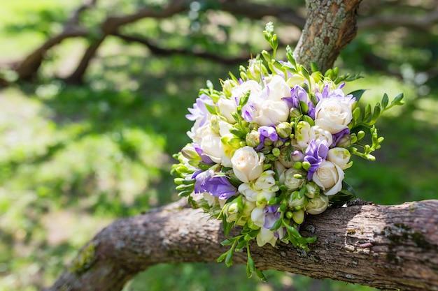 Brautstrauß mit rosen und freesien blüht, traditionelle blumenzusammensetzung für hochzeitszeremonie.