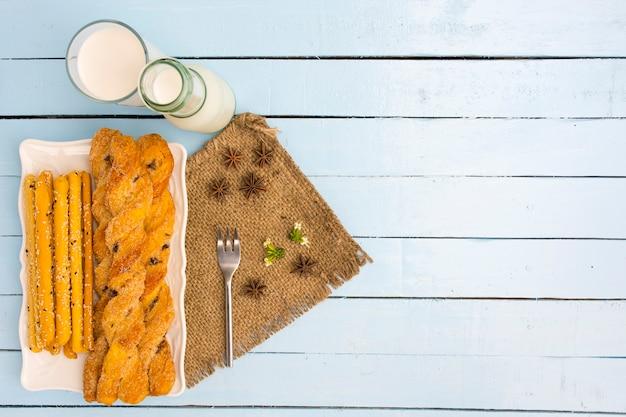Breadsticks und milch auf himmelblauen tabellenhintergrund. snack mit mahlzeit oder lebensmittel