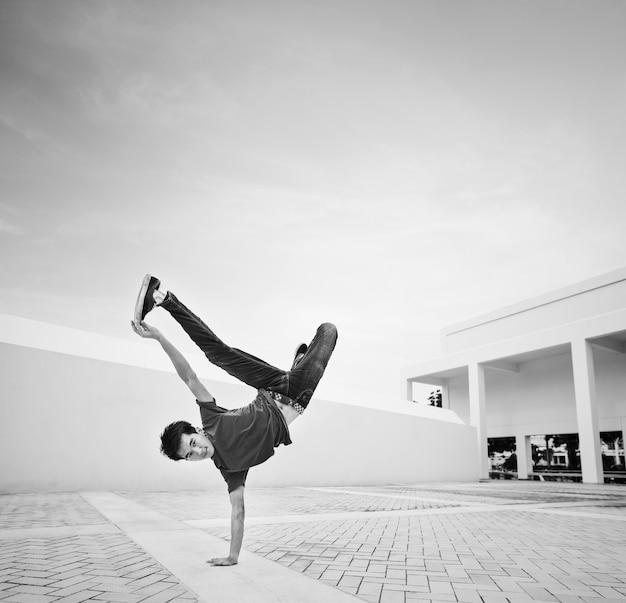 Breakdance des jungen mannes an einer dachspitze
