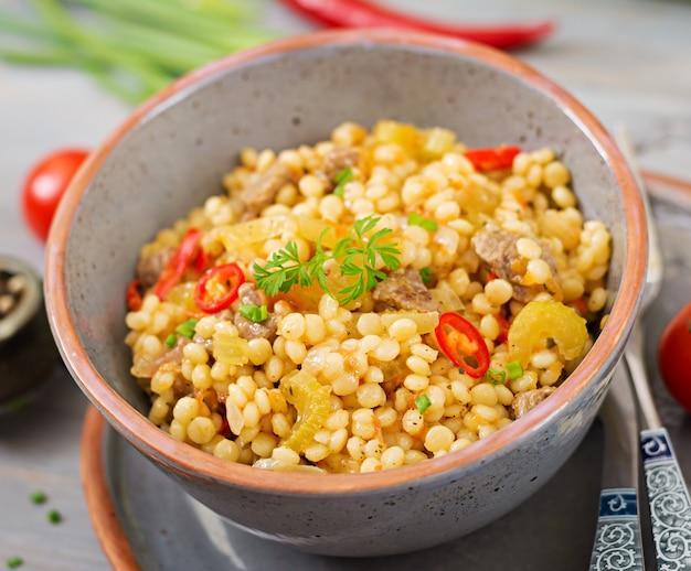 Brei aus türkischem couscous mit rindfleisch und gemüse. diätmenü.