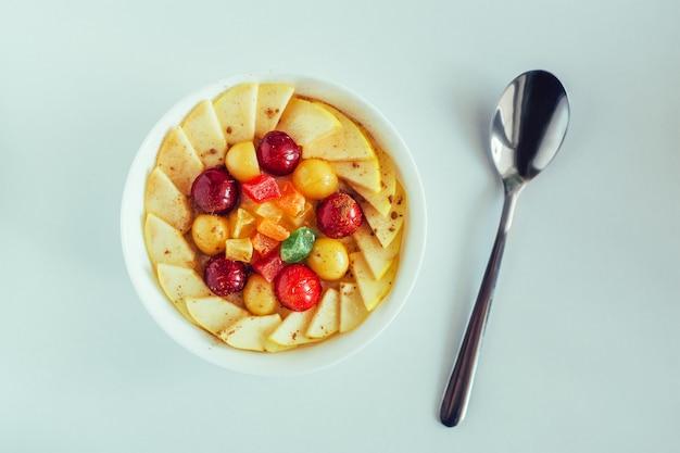 Brei mit kirsche, apfel und kandierten früchten in der weißen schüssel auf weißem hintergrund