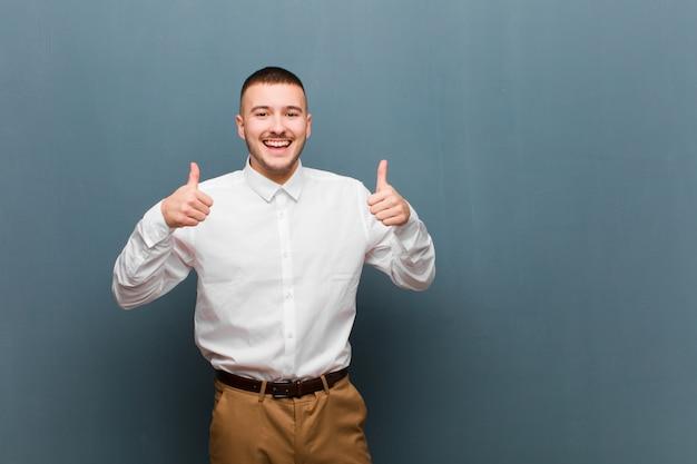 Breit lächelnd glücklich, positiv, selbstbewusst und erfolgreich, mit beiden daumen hoch