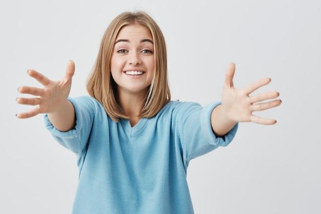 Breit lächelnd mit zähnen hübsche junge europäische frau gekleidet in blauen pullover, der ihre arme ausstreckt, posiert. positive emotionen und gefühle.