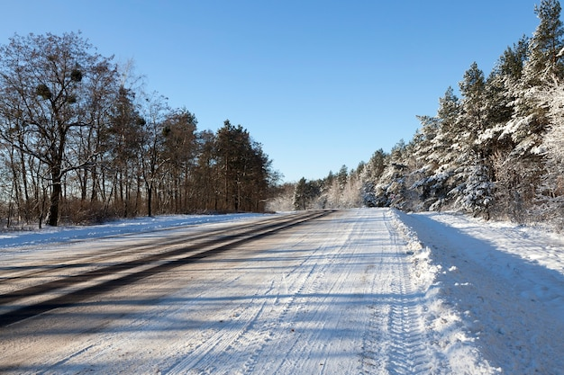 Breite asphaltstraße, auf der es spurrillen von autos auf der straße gibt, im wald in der wintersaison, blauer himmel im hintergrund