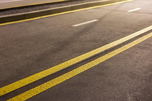 Breite helle doppelte gelbe markierungszeichenlinie entlang der modernen breiten glatten leeren asphaltautobahnstraße, die sich bis zum horizont erstreckt. geschwindigkeit, sicherheit, komfortable fahrt und professionelles straßenbaukonzept.