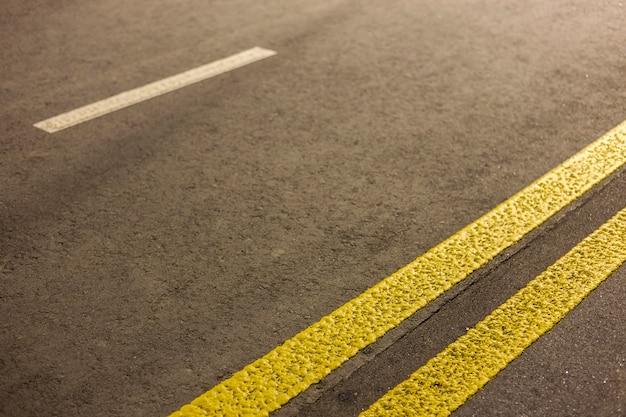 Breite helle doppelte gelbe markierungszeichenlinie entlang der modernen breiten glatten leeren asphaltautobahnstraße, die sich zum horizont erstreckt. geschwindigkeit, sicherheit, komfortable fahrt und professionelles straßenbaukonzept.