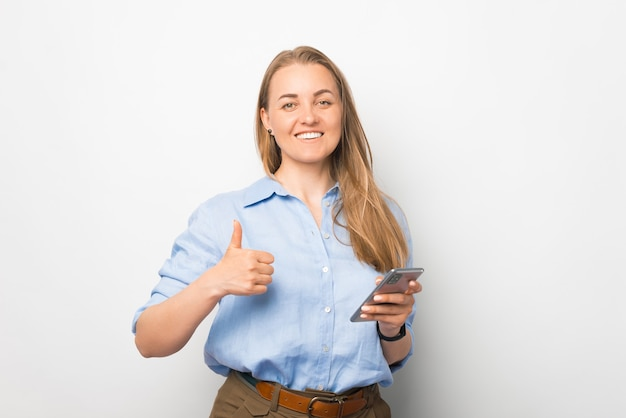 Breite lächelnde geschäftsfrau hält ein intelligentes telefon und zeigt die daumen-oben-geste.