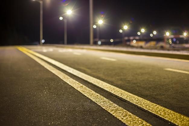 Breite moderne glatte leere beleuchtete mit straßenlaternen asphaltstraße mit hellweißer markierungszeichenlinie bei nacht. geschwindigkeit, sicherheit, komfortable fahrt und professionelles straßenbaukonzept.