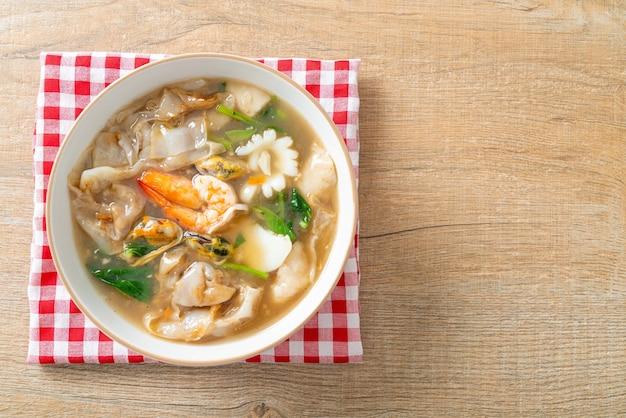 Breite reisnudeln mit meeresfrüchten in soße - asiatische küche asian