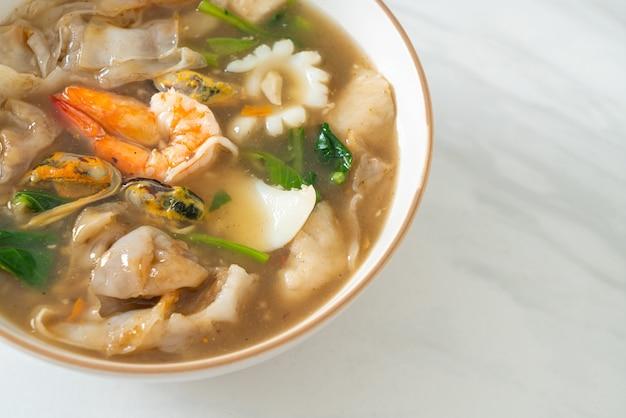 Breite reisnudeln mit meeresfrüchten in soße - asiatische küche