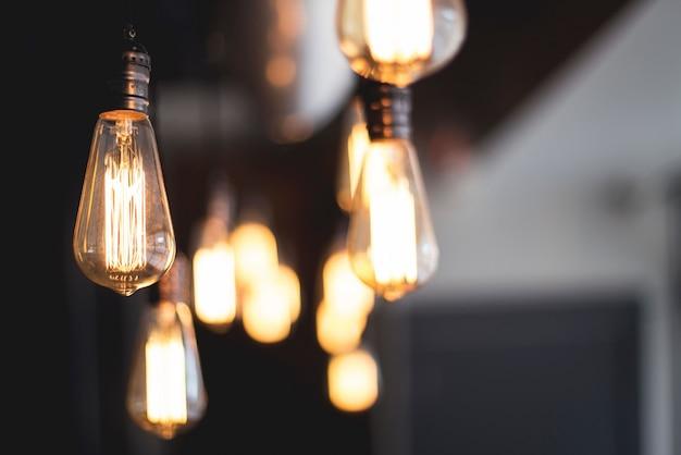 Breite selektive nahaufnahme von beleuchteten glühbirnen, die von einer decke hängen
