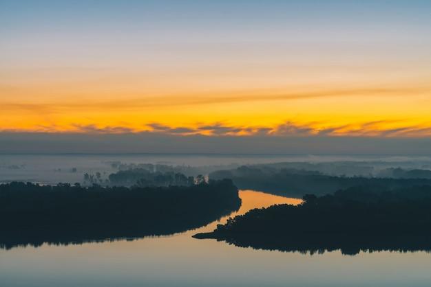 Breiter fluss fließt entlang ufer mit wald unter dichtem nebel.