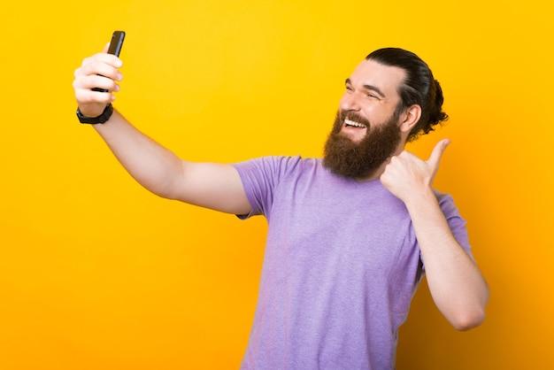 Breiter lächelnder junger mann macht ein selfie über gelbem hintergrund.