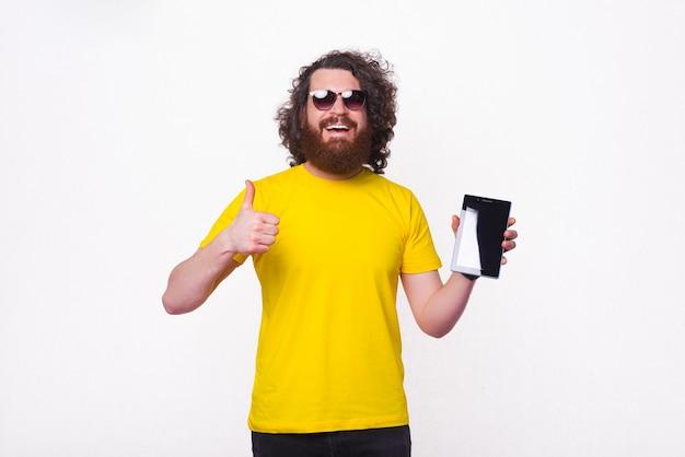 Breiter lächelnder mann zeigt tablet-bildschirm und daumen nach oben.