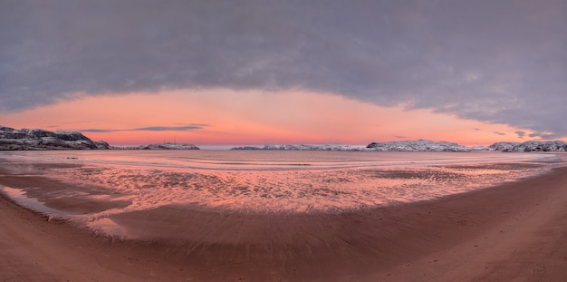 Breiter panoramablick auf den wintersonnenuntergang mit erstaunlicher magentafarbener farbe über dem fjord.