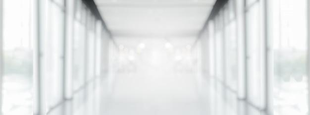Breiter weißer grauer unscharfer leerer abstrakter korridorweg-hintergrund vom perspektivischen gebäudeflur