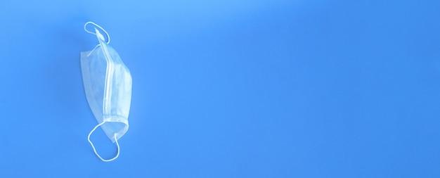 Breites banner mit dem bild einer medizinischen schutzmaske nahaufnahme auf einer blauen wand. es ist platz für text. gesundheits-, medizin- und virenschutzkonzept.