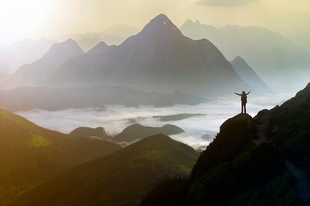 Breites bergpanorama. kleines schattenbild des touristen mit rucksack auf felsigem berghang.