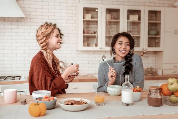Breites lächeln zeigen. lächelndes blondes mädchen, das frühstück mit ihrem lächelnden gutaussehenden freund beim sitzen in der küche hat