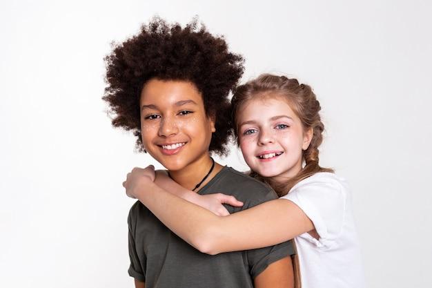 Breites lächeln. zufriedene, gut aussehende kinder, die zeit miteinander im studio verbringen und in engem kontakt stehen