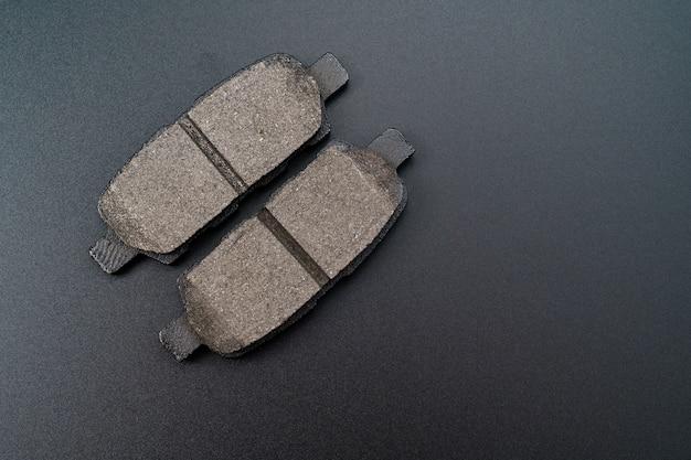 Bremsbelag gegen auf schwarzem hintergrund. teil des bremssystems, hauptfunktionskomponente. anti-rückschlag-betonung zur zusätzlichen fixierung des fahrzeugs beim parken. autoteile shop. auto-werkstatt