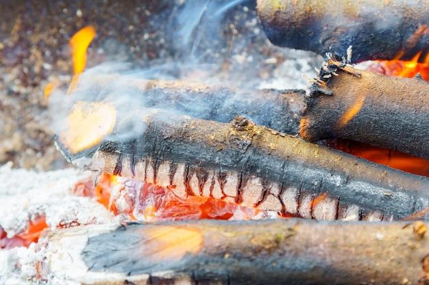 Brennen im feuerbrett. lagerfeuer mit flamme, rauch, holzbohlen und holzkohlenglut. fotonahaufnahme mit selektivem fokus und unscharfem hintergrund