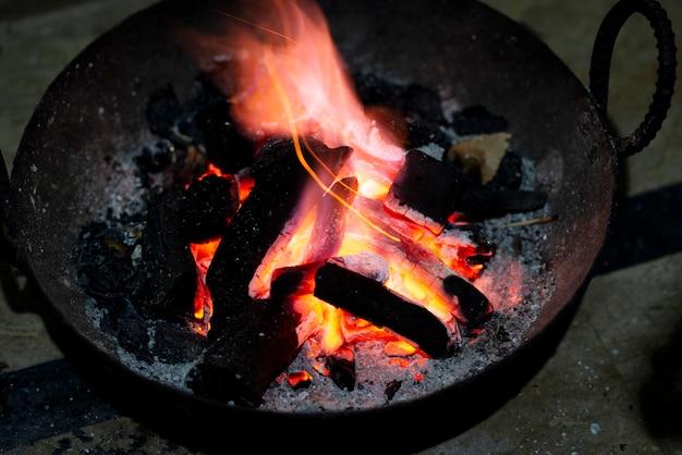 Brennen von holzkohle in einem eisenofen zum heizen zu hause. rot gebrannte holzkohle und asche, um den raum zu erwärmen.
