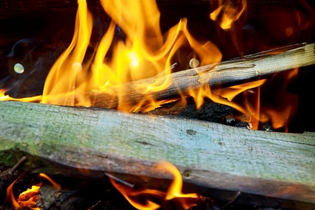 Brennende flammen und glühende kohle beim grillen, warmes orange feuer mit holzstücken