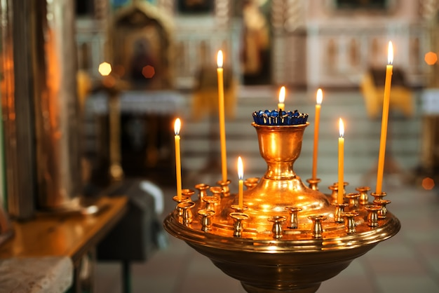 Brennende gelbe kerzen in der orthodoxen kirche