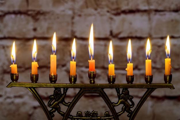 Brennende hanukkah-kerzen in einem menorah auf bunten kerzen von einem menorah