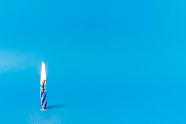Brennende kerze auf blauem hintergrund