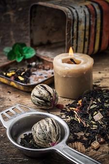 Brennende kerze auf dem hintergrund des zerstreuten tees mit kalk und minze in der rustikalen art.