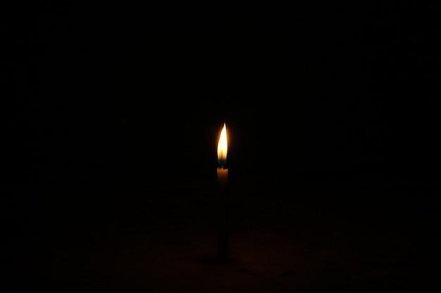 Brennende kerze auf einem dunklen hintergrund