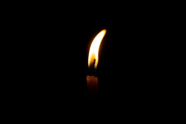 Brennende kerze auf schwarzem hintergrund