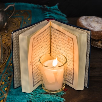 Brennende kerze der nahaufnahme nahe geöffnetem koran