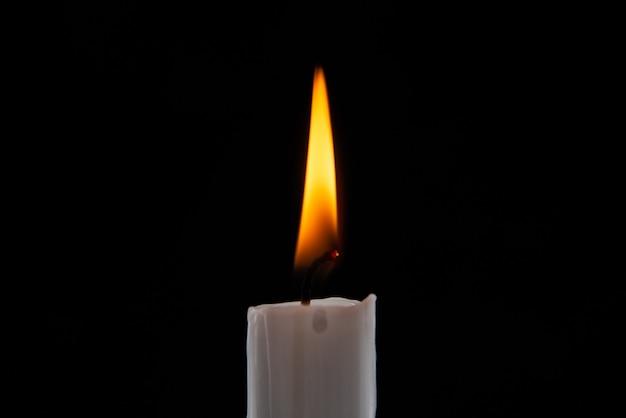 Brennende kerze der vorderansicht auf dunkler oberfläche