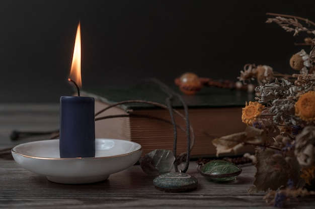 Brennende kerze, ein buch, trockene kräuter und magische steine. set für hexen.