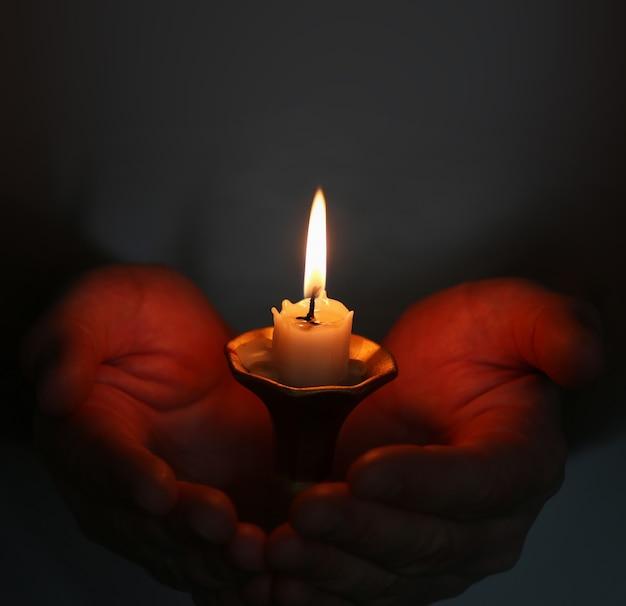 Brennende kerze im handreligionskonzept eines mannes