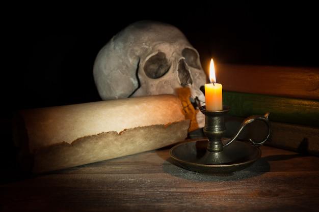Brennende kerze im kerzenständer nahe alter buch- und weinleserolle auf schwarzem hintergrund