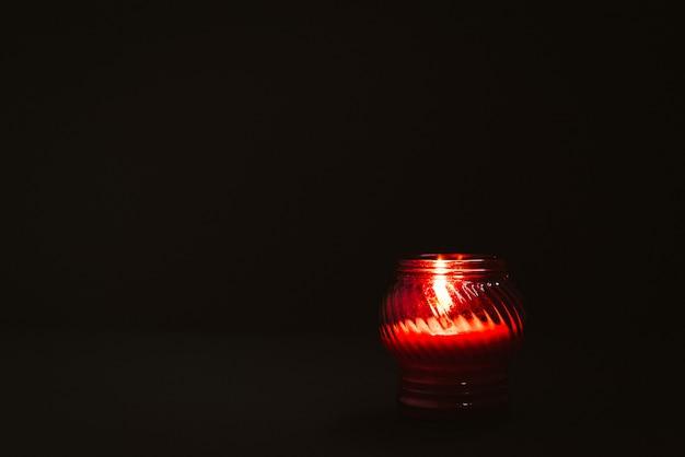 Brennende kerze im roten glaskerzenhalter auf schwarzem