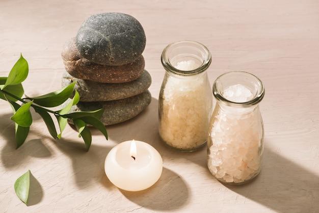 Brennende kerze im wasser spa-einstellung mit salz und kieselsteinen