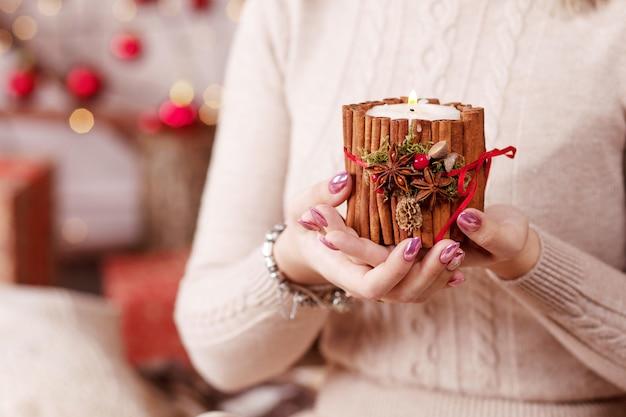 Brennende kerze in den händen eines mädchens. weihnachtskerze. weihnachtsdekoration. hände der frau, die schöne kerze mit feuer anhalten. kopieren sie platz