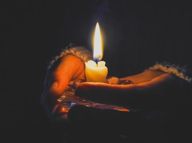 Brennende kerze in den weiblichen händen in der nacht.
