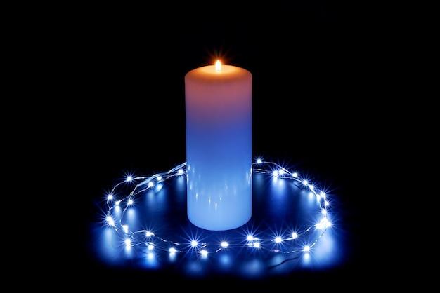 Brennende kerze in der beleuchtung von lichtern auf einem dunklen schwarz.