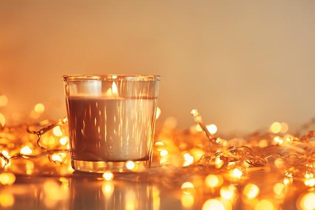 Brennende kerze mit goldener girlande beleuchtet im bokeh auf dunklem hintergrund