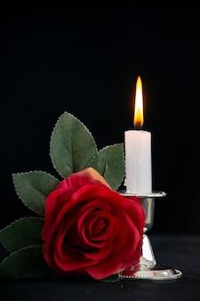 Brennende kerze mit roter blume als erinnerung auf dunkler oberfläche