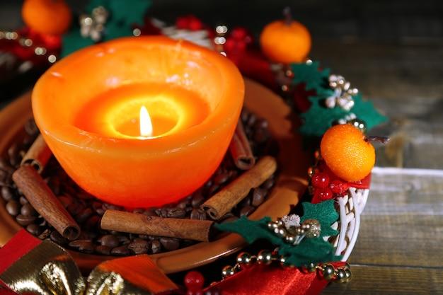 Brennende kerze mit weihnachtsschmuck auf farbigem holzhintergrund