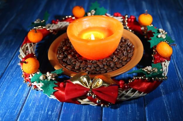 Brennende kerze mit weihnachtsschmuck auf farbigem holztisch